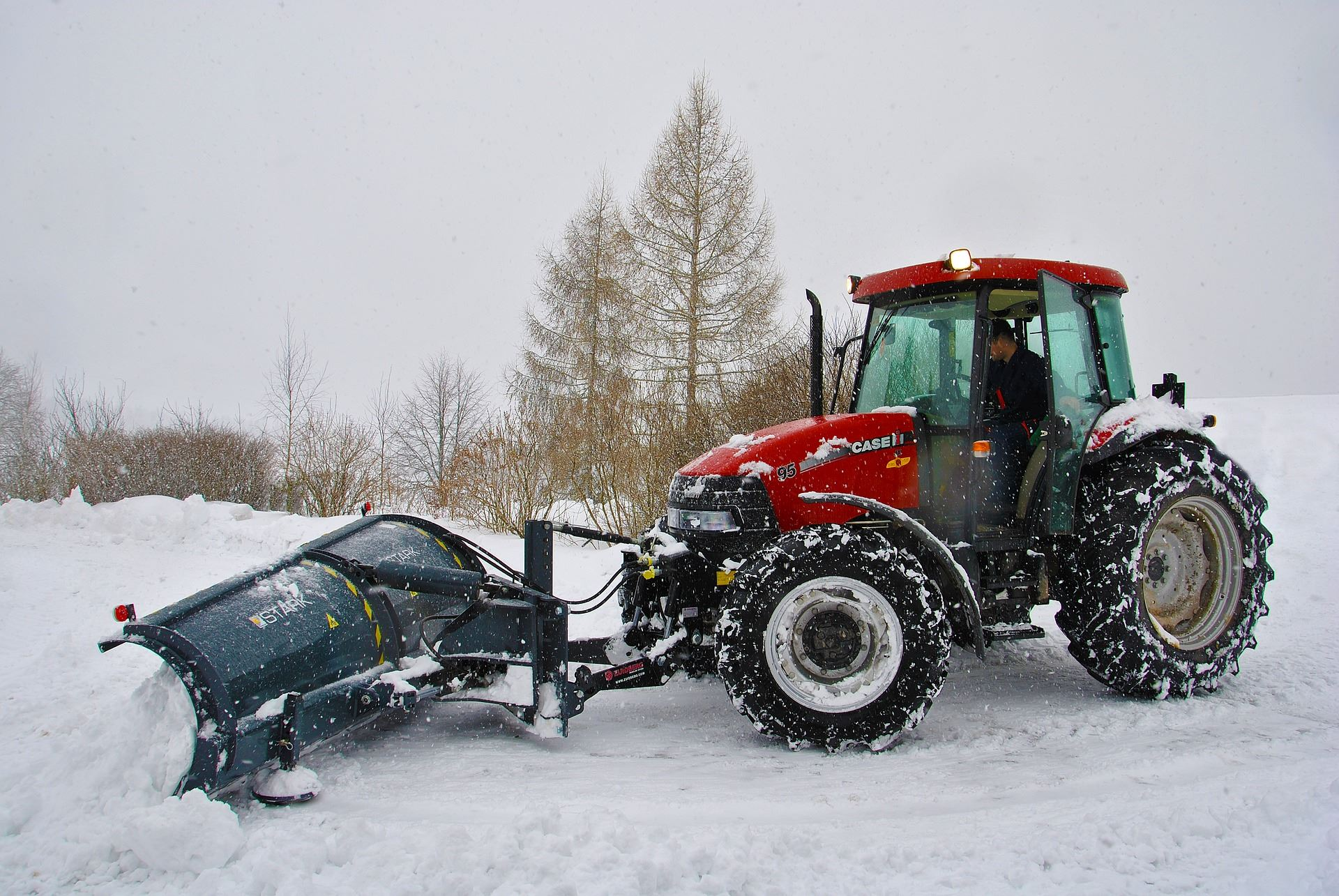 Tractor with snow plow attachment plowing snow image