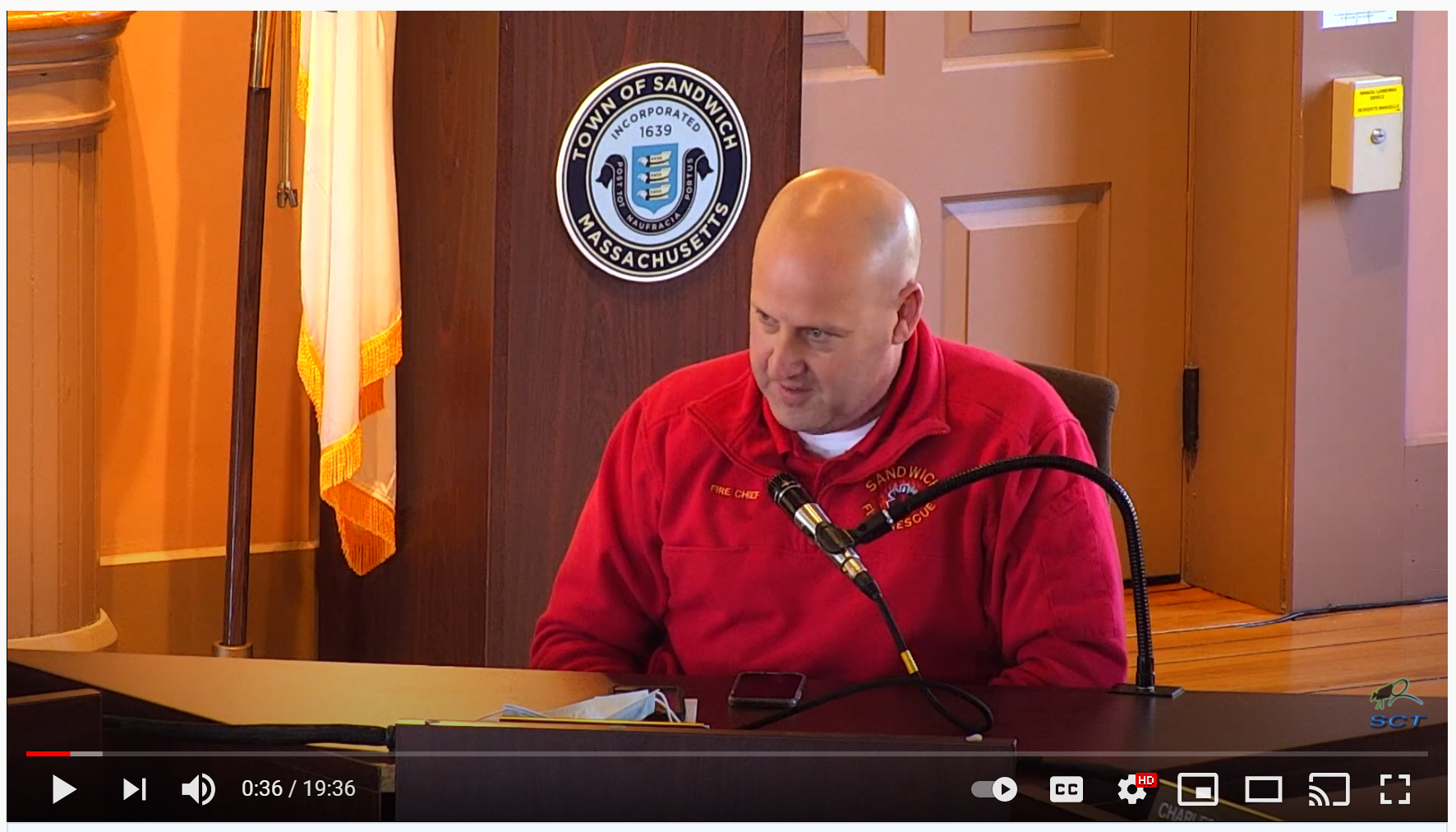 Fire Chief in red shirt speaking into a microphone